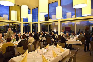 Gäste sitzen abends an den Tischen im Innenraum