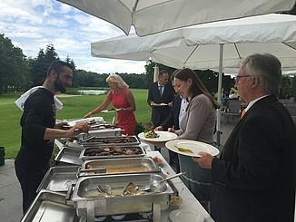 Gäste im Außenbereich werden am warmen Buffet bedient